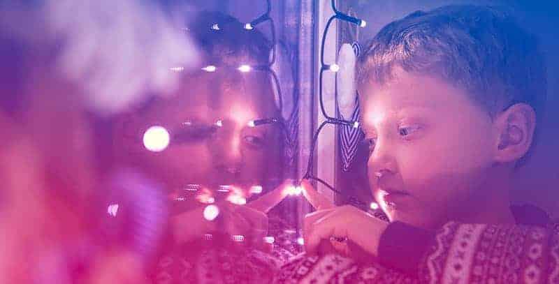 Enfant triste regardant par la fenêtre décorée pour Noël