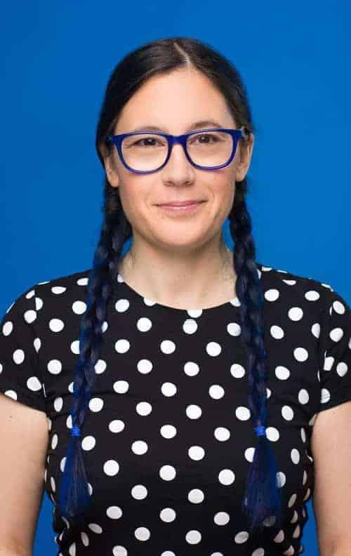 Femme blanche autiste souriante avec lunettes bleues et tresses bleues